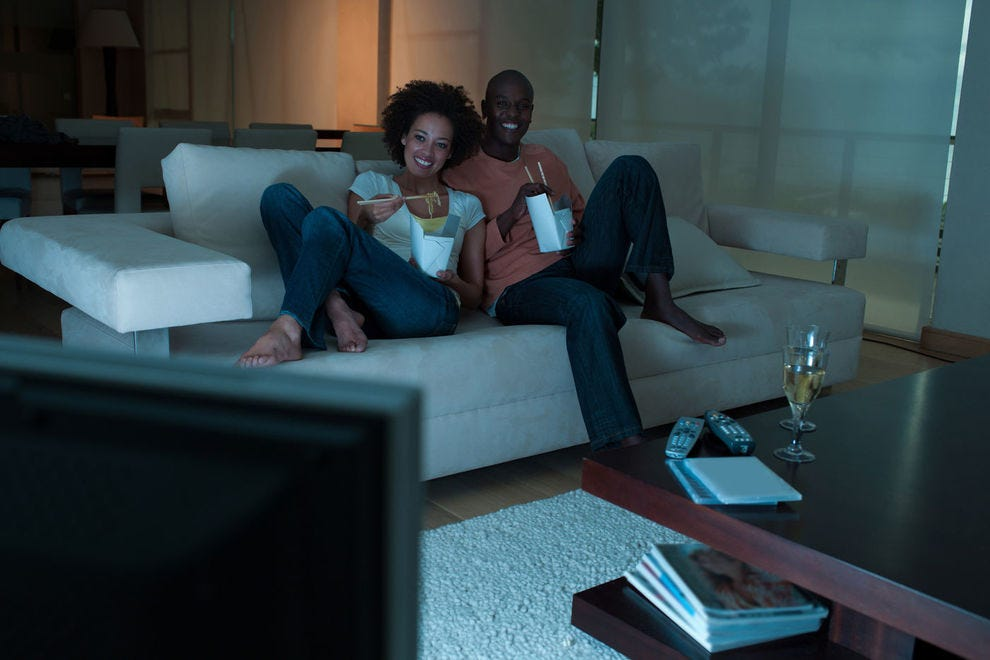 Couple watching TV and eating food on the couch