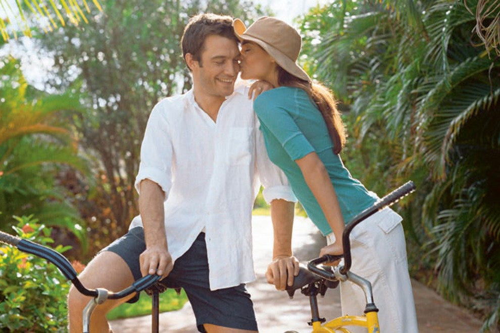 A couple enjoying a bike ride at Excellence Playa Mujeres.