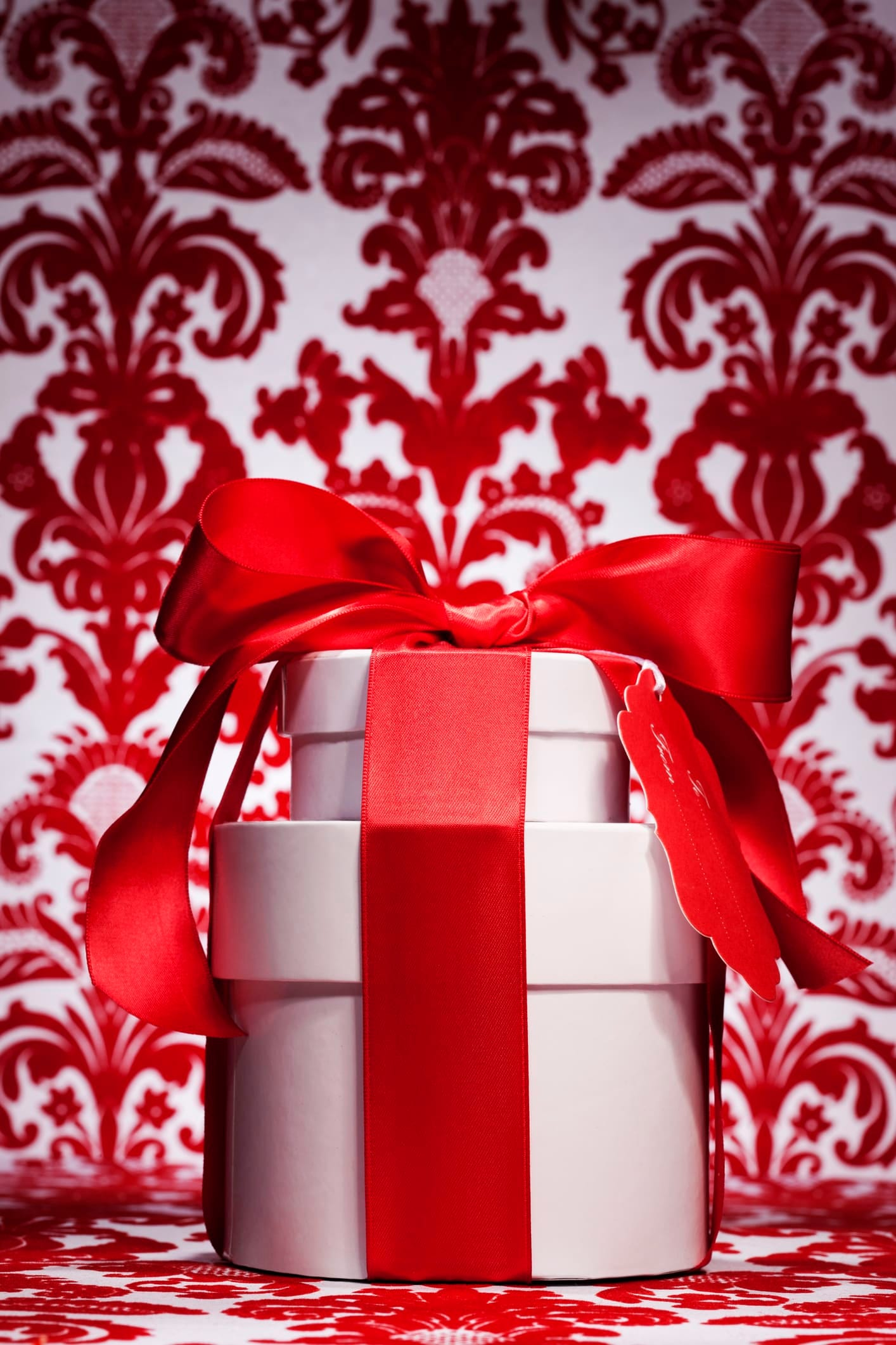 white present wrapped with red bow and ornate red and white background